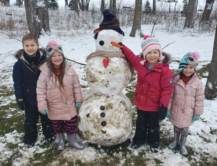 Four little kids standing by their snowman Ben
