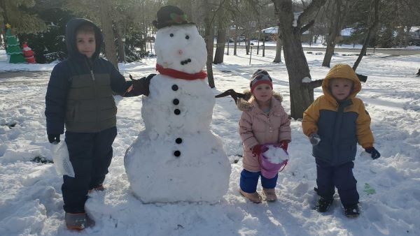 four kids standing by their snowman