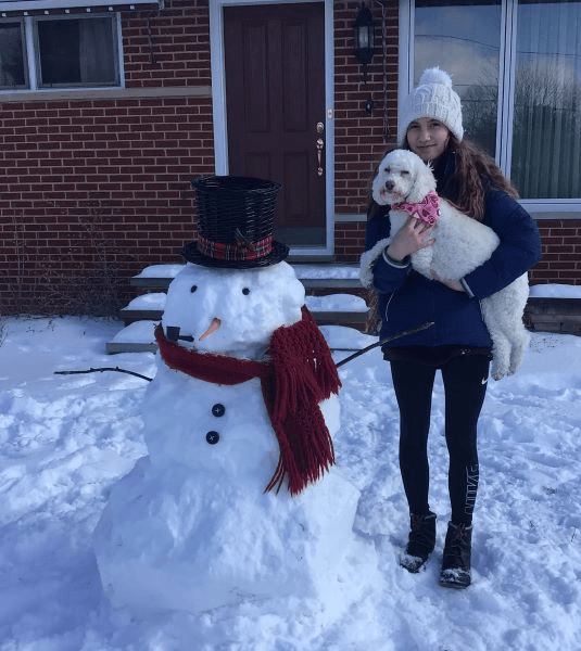 a snowman, girl holding her dog