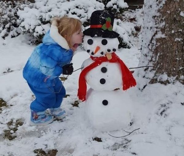 Snowman with a little girl kissing his cheek