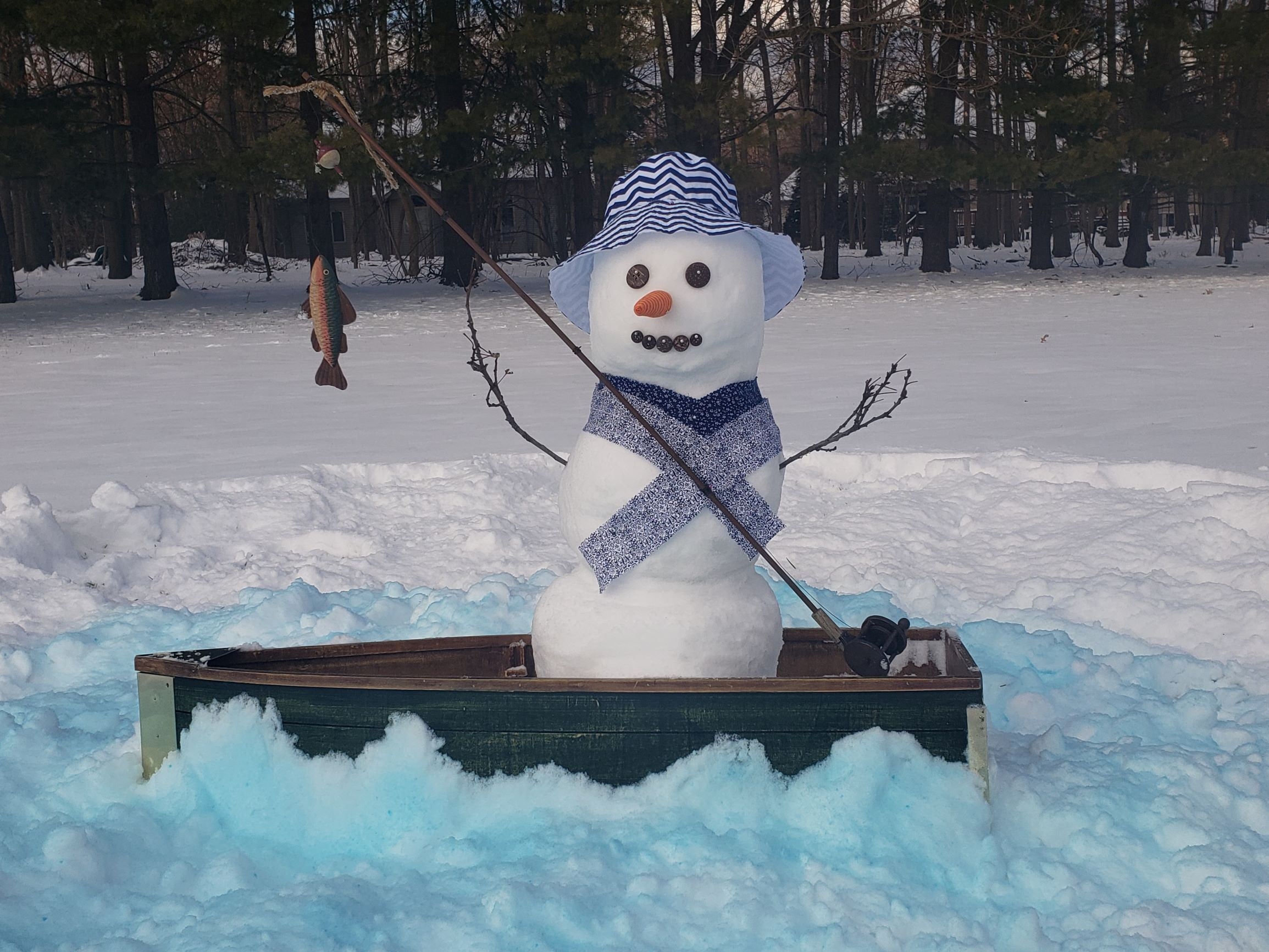 Snowman in a boat fishing