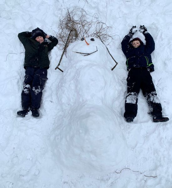 Flat snowman laying on his back on the ground with two boys