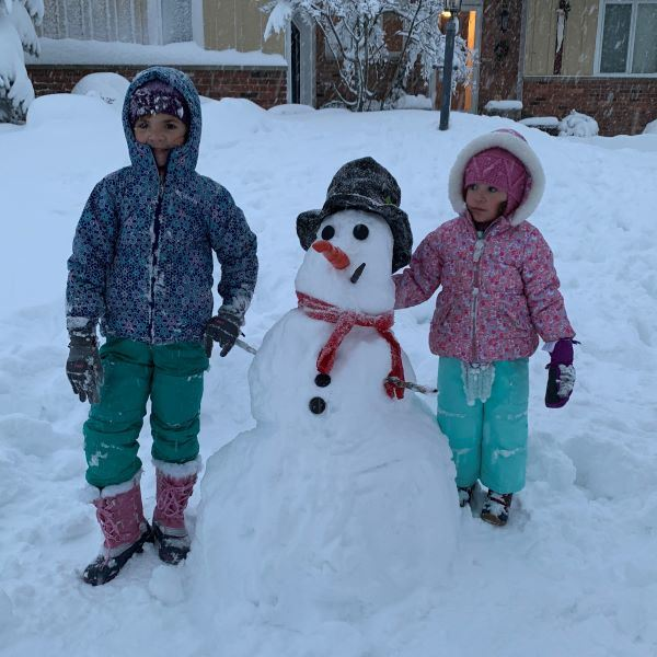 a snowman with two little girls