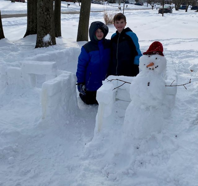 boys with 2021 snow fort and snowman